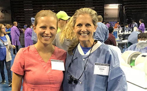 two smiling women at a dental convention