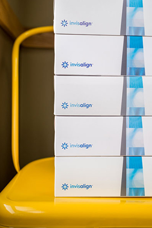 five boxes of Invisalign on a yellow chair