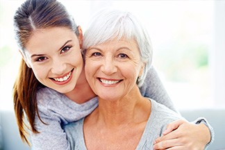 younger woman with her arm around an older woman smiling
