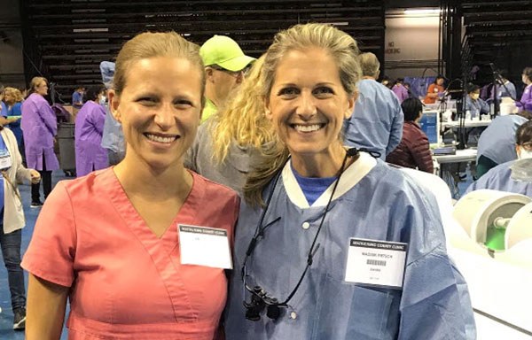 two smiling women at a dental conference